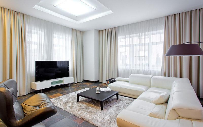Дизайн зала в частном доме с двумя окнами